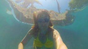 Nadadas felices de la muchacha feliz subacuáticas en la piscina Luz del sol a través del agua almacen de metraje de vídeo