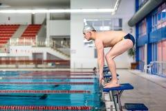 Nadador activo que consigue listo para saltar en piscina, comienzo de la competencia imágenes de archivo libres de regalías