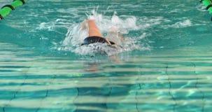 Nadador apto que hace el movimiento delantero en la piscina almacen de video
