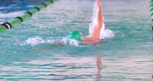 Nadador apto que hace el movimiento trasero en la piscina almacen de video