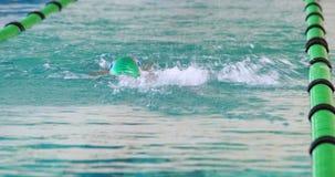 Nadador apto que hace el movimiento trasero en la piscina almacen de metraje de vídeo