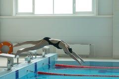 Nadador de la chica joven, ese salto y el zambullirse en piscina del deporte interior imagenes de archivo