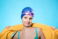 Nadador de la muchacha en un casquillo de natación y gafas del salto Ella está sosteniendo una toalla amarilla en sus hombros El  Foto de archivo
