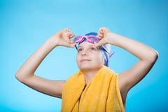 Nadador de la muchacha en un casquillo y vidrios de baño La muchacha sostiene los vidrios para zambullirse Ella mira para arriba Foto de archivo