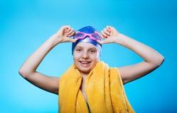Nadador de la muchacha en un casquillo y vidrios de baño La muchacha sostiene los vidrios para zambullirse Ella ríe El concepto d Imagen de archivo libre de regalías