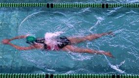 Nadador de sexo femenino apto que hace el movimiento de pecho en la piscina almacen de metraje de vídeo