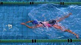 Nadador de sexo femenino apto que hace el movimiento de pecho en piscina almacen de metraje de vídeo