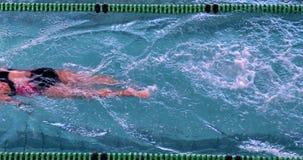 Nadador de sexo femenino apto que hace el movimiento delantero en la piscina metrajes