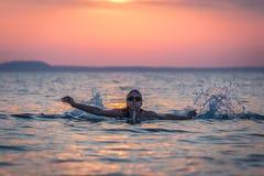 Nadador de sexo femenino en el mar en la puesta del sol Imagenes de archivo