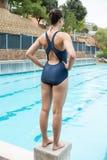 Nadador de sexo femenino que se prepara para zambullirse en piscina Fotos de archivo