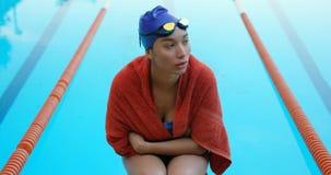 Nadador de sexo femenino que se sienta cerca de la piscina 4k almacen de metraje de vídeo