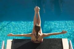 Nadador de sexo femenino que se sienta en tablero de la zambullida Fotos de archivo libres de regalías