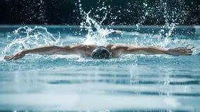 Nadador dinámico y apto en el casquillo que respira realizando el movimiento de mariposa foto de archivo libre de regalías