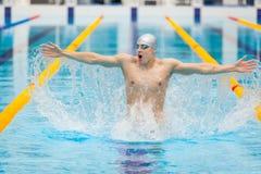Nadador dinámico y apto en la ejecución de respiración del casquillo saltando el agua, concepto de victoria, libertad, felicidad Imagen de archivo