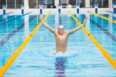 Nadador dinâmico e apto na execução de respiração do tampão saltando a água, conceito da vitória, liberdade, felicidade Imagem de Stock