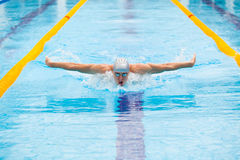 Nadador dinámico y apto en el casquillo que respira realizando el movimiento de mariposa Imagen de archivo
