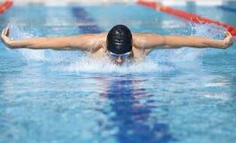 Nadador en el casquillo que respira realizando el movimiento de mariposa Foto de archivo