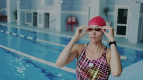 Nadador fêmea profissional novo que põe sobre seus óculos de proteção em sua cara para a flutuação subaquática, veste o roupa de  video estoque