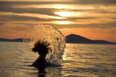 Nadador que salpica en la puesta del sol Imagenes de archivo