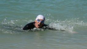Nadador que viene al extremo de la ruta en una natación de la competencia en un lago almacen de metraje de vídeo