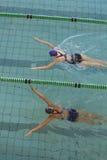 Nadadores de sexo femenino que compiten con en la piscina Fotografía de archivo