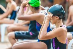 Nadadores de sexo femenino que consiguen listos y que esperan para nadar fotos de archivo