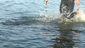 Nadadores dos atletas que mudam a disciplina da raça da natação a biking no movimento lento do rio filme