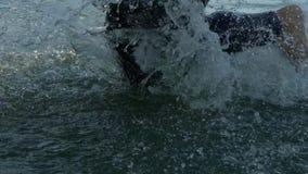 Nadadores dos atletas que mudam a disciplina da raça da natação a biking no movimento lento do rio vídeos de arquivo