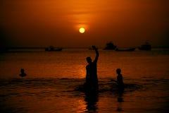 Nadadores en la puesta del sol Fotos de archivo