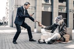 Nadaremny bogaty człowiek robi selfie on z brudnym bezdomny zdjęcia stock