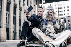 Nadaremny bogaty człowiek w kostiumu robi selfie darowizna pieniądze obrazy royalty free