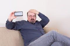 Nadaremny mężczyzna bierze selfie na jego smartphone obraz stock