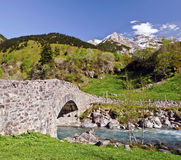 Nadau bridge through Gave de Gavarnie river. Is a stone bridge on the way from Gavarnie village to the mountain Circus, Ambama forest, slopes and snowy tops of stock photography
