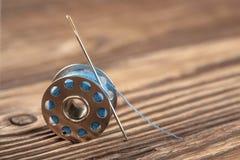 Nadel und Spule auf einem hölzernen Hintergrund Lizenzfreie Stockbilder