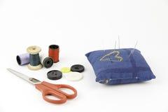Nadelkissen mit Nadeln, Knöpfen, Scheren und Threads Lizenzfreie Stockbilder