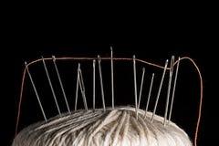 Nadeln und orange Baumwolle verlegt auf einer weißen Baumwollschrittballmakronahaufnahme Lizenzfreies Stockbild