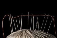 Nadeln und orange Baumwolle verlegt auf einer weißen Baumwollschrittballmakronahaufnahme Lizenzfreie Stockfotografie