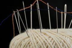 Nadeln und orange Baumwolle verlegt auf einer weißen Baumwollschrittballmakronahaufnahme Lizenzfreie Stockfotos
