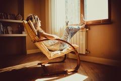 Nadenkend concept De droevige vrouw verloor in het gedachte lounging als comfortabele moderne voorzitter bekijkend venster in woo Stock Foto