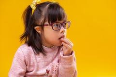 Nadenkend donker-haired kind die met abnormaliteit snacks eten stock afbeeldingen