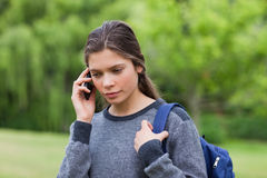 Nadenkend jong meisje die haar mobiele telefoon met behulp van Stock Foto's