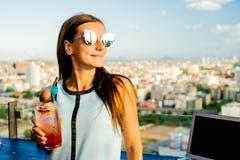 Nadenkend jong meisje die smoothie smoothie drinken Terwijl het zitten bij een lijst in een koffie op het dak met mooi royalty-vrije stock foto's