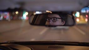 Nadenkend jong zakenmans gezicht in een achteruitkijkspiegel, die een auto drijven bij nacht stock footage