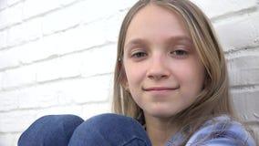 Nadenkend Kindportret, het Glimlachen Jong geitjegezicht dat Blonde Bored Meisje in camera kijkt stock footage