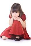 Nadenkend klein meisje in rode kleding Royalty-vrije Stock Afbeeldingen