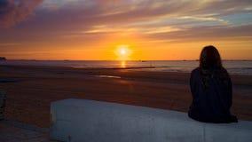 Nadenkend meisje die op de zonsondergang letten Royalty-vrije Stock Afbeelding
