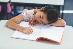 Nadenkend schoolmeisje met boek stock foto