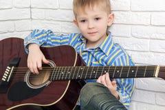 Nadenkend weinig jongen die en de gitaar zitten spelen Stock Afbeelding