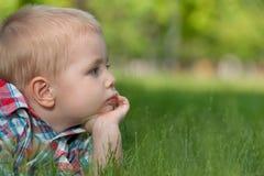 Nadenkend weinig jongen op het gras Stock Foto's