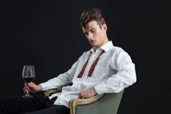 Nadenkende androgene mensenzitting op stoel met glas wijn Stock Afbeeldingen